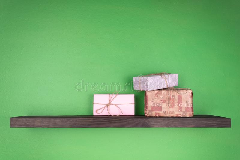 Três caixas de presente de cores diferentes arranjadas em um grupo em uma prateleira preta ajustada na parede verde fotografia de stock
