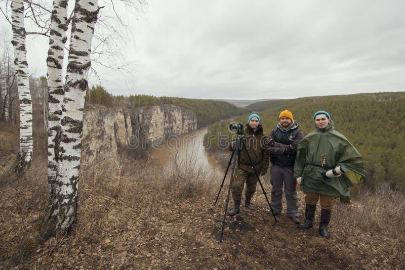 Três camermen novos do amigo exteriores - realização na floresta selvagem da montanha fotos de stock