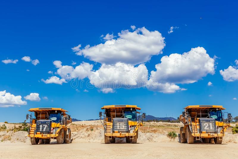 Três caminhões de descarregador grandes em seguido foto de stock