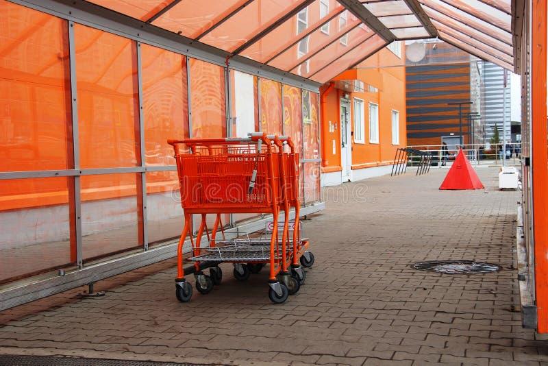 três carrinhos de compras para bens perto da loja da construção na laranja fotos de stock