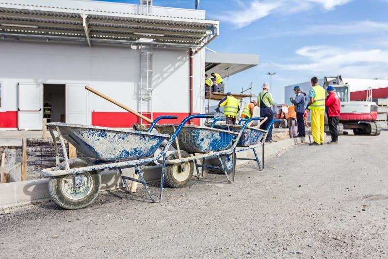 Três carrinhos de mão com as ferramentas para limpar são alinhados imagens de stock royalty free