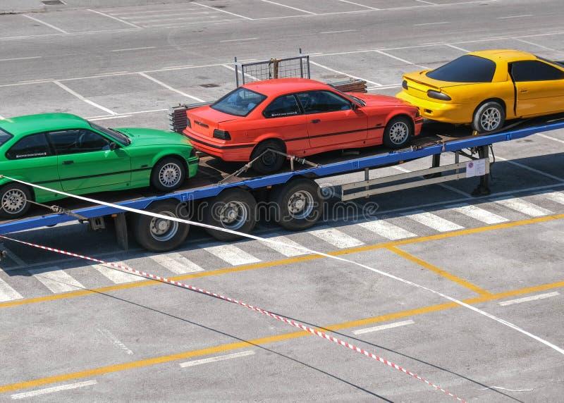 Três carros coloridos em um reboque fotos de stock royalty free