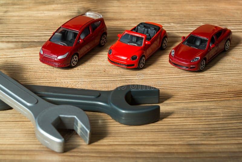 Três carros do brinquedo e chaves inglesas vermelhos do brinquedo em um fundo de madeira fotos de stock