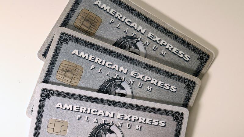 Três cartões da platina do Amex de American Express em uma tabela branca foto de stock royalty free
