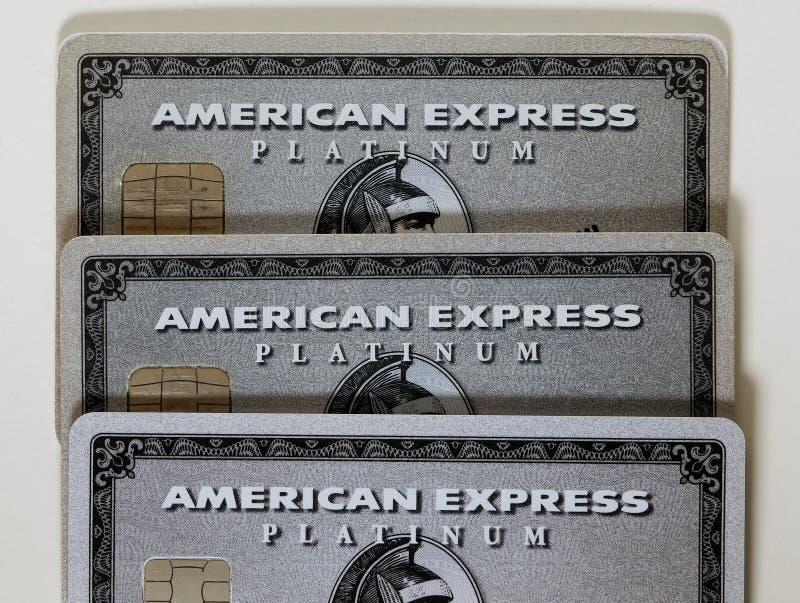 Três cartões da platina do Amex de American Express em uma tabela branca foto de stock