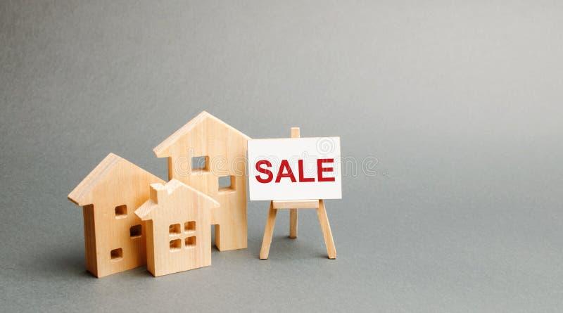 Três casas de madeira e um suporte com a VENDA da inscrição Vendendo uma HOME Anúncio da venda e do potencial da atração fotografia de stock