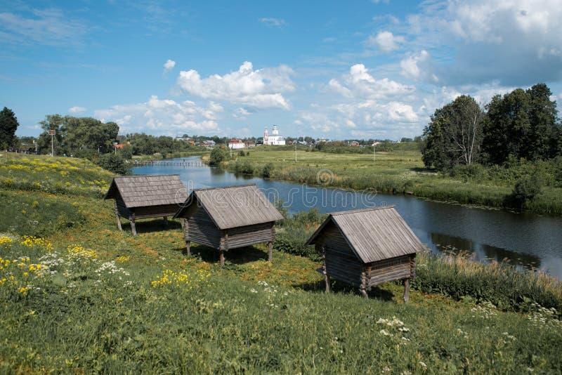 Três casas de madeira velhas pequenas em pernas de pau altos pelo rio foto de stock