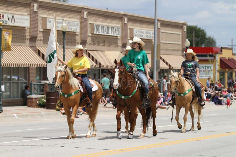 Três cavaleiros de horseback em uma parada na cidade pequena América foto de stock