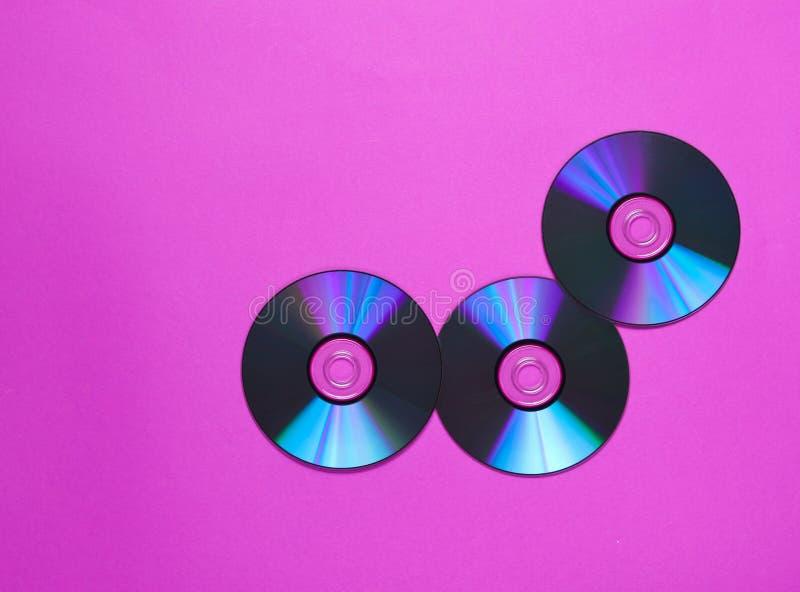 Tr?s CD' s em um fundo cor-de-rosa foto de stock