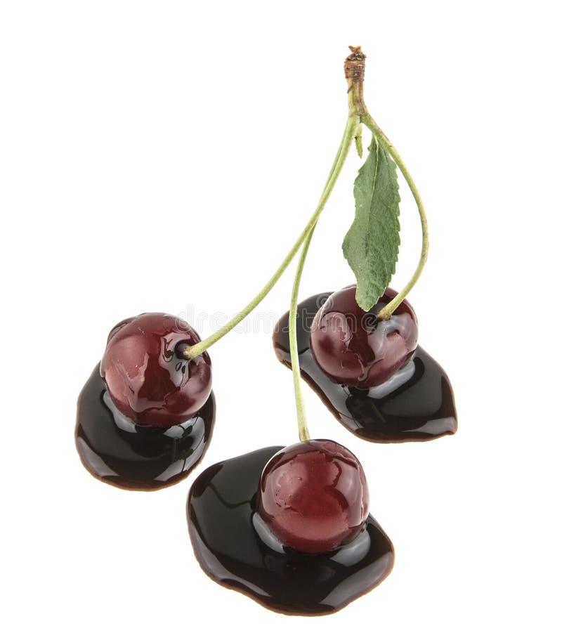 três cerejas no chocolate isolado no branco imagem de stock royalty free