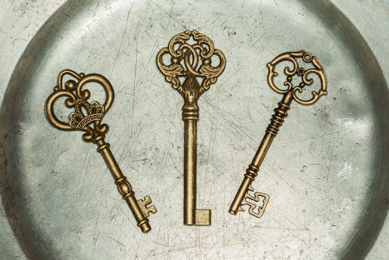 Três chaves douradas na placa do ferro fotos de stock royalty free