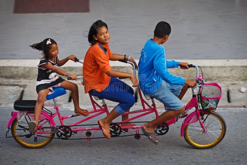 Três childred na bicicleta em tandem em uma estrada imagem de stock