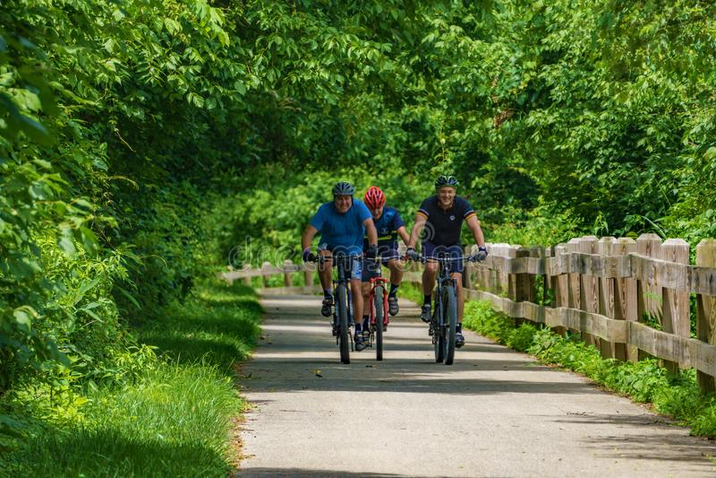 Três ciclistas com capacetes protetores foto de stock royalty free