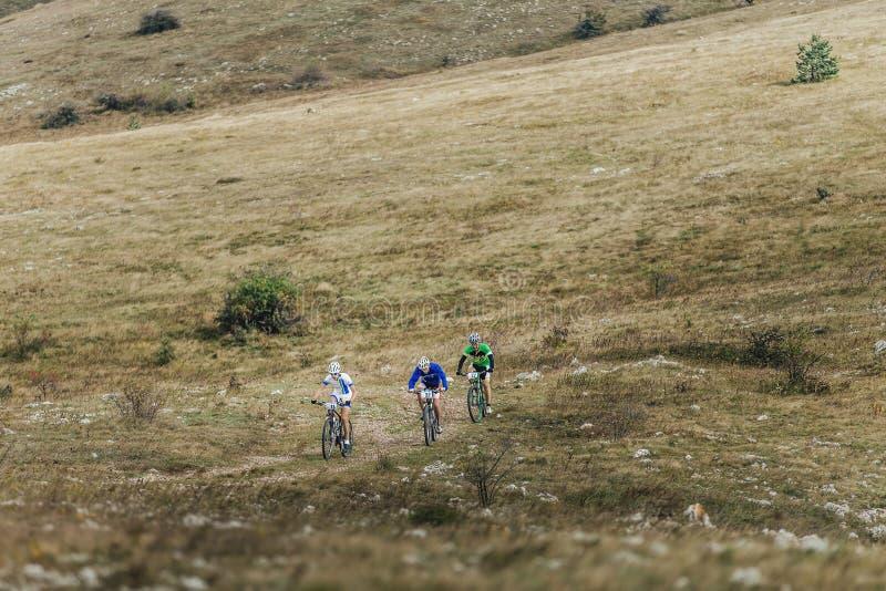 Três ciclistas dos cavaleiros em um mountainbike montam o vale nas montanhas fotos de stock
