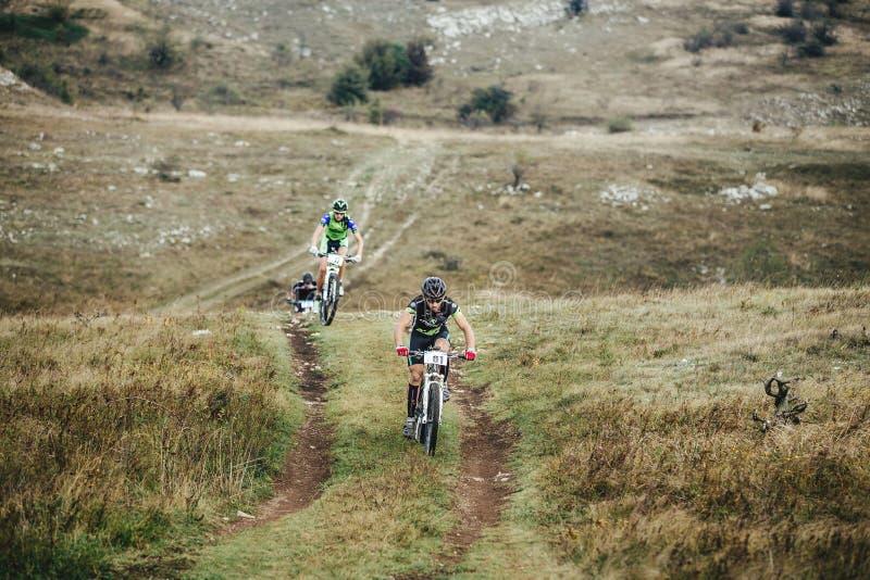 Três ciclistas em passeios dos Mountain bike de subida imagens de stock royalty free