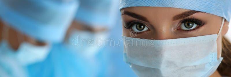 Três cirurgiões no trabalho que opera-se no teatro cirúrgico imagem de stock royalty free