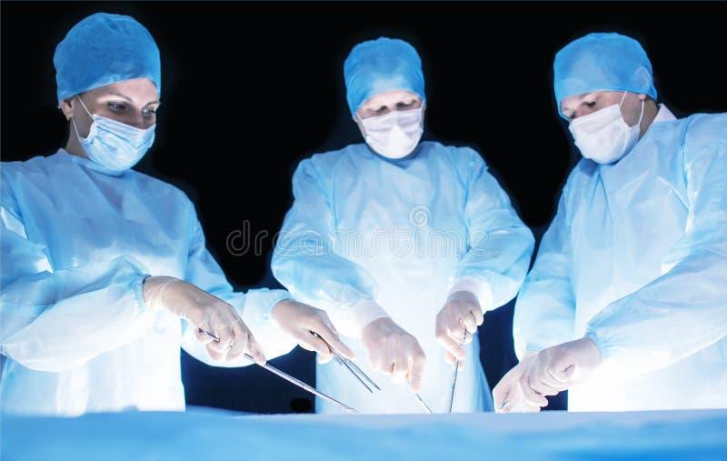 Três cirurgiões, um homem e uma mulher, executam a cirurgia na sala de operações remover e para transplantar os órgãos humanos, r imagens de stock