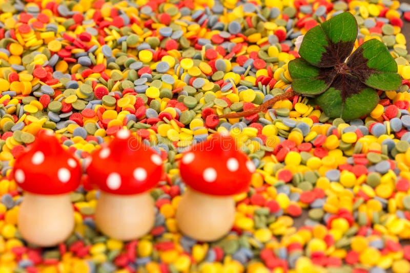 Três cogumelos de voo e um trevo folheiam em confetes coloridos fotografia de stock