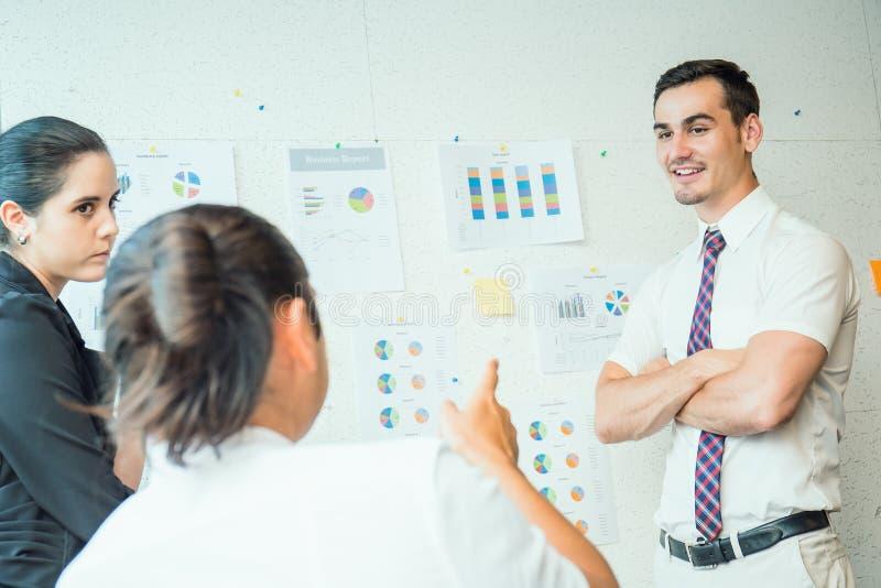 Três colegas do trabalho discutem com a carta da estratégia imagens de stock