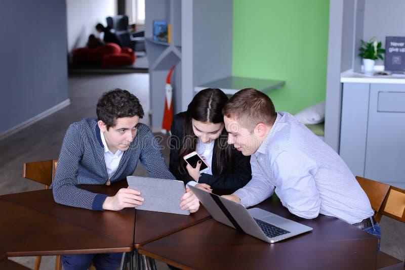 Três colegas, a fêmea e dois homens novos sentam-se na rede social fotos de stock royalty free