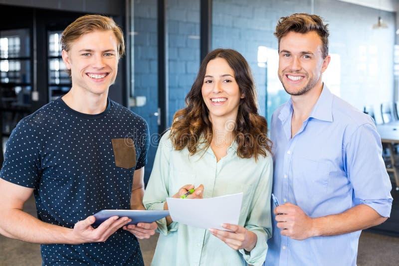 Três colegas seguros que discutem no escritório imagens de stock