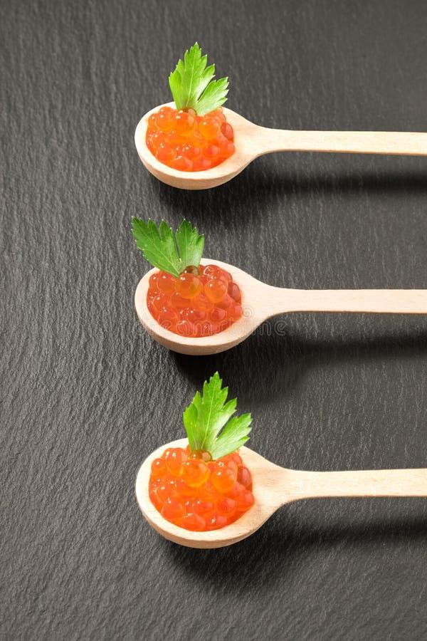 Três colheres de madeira com caviar e salsa salmon foto de stock royalty free