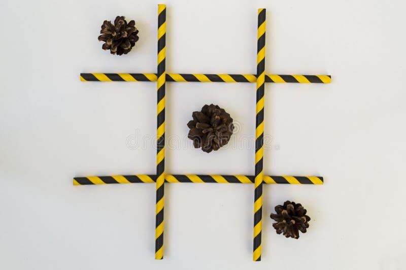 Três cones de abeto marrons encontram-se em seguido em um jogo do tique-TAC-dedo do pé, em uma grade em um fundo branco A grade c fotografia de stock royalty free