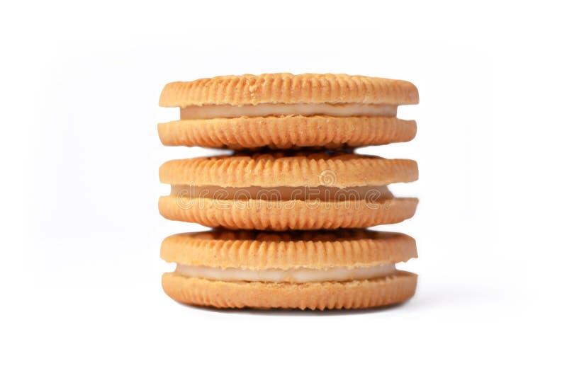 Três cookies empilhadas enchidas com o creme branco no fundo branco imagens de stock royalty free