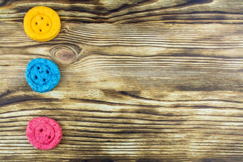 Três cookies sob a forma dos botões de cores diferentes encontram-se sobre fotografia de stock