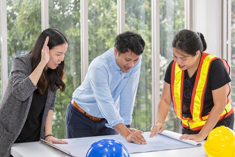 Três coordenadores que trabalham a sala de reunião no escritório Três trabalhadores estão falando o plano da construção Carpintei imagens de stock royalty free