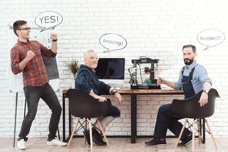 Três coordenadores trabalham com uma impressora 3d em um laboratório moderno Têm nuvens de conversação sobre suas cabeças foto de stock
