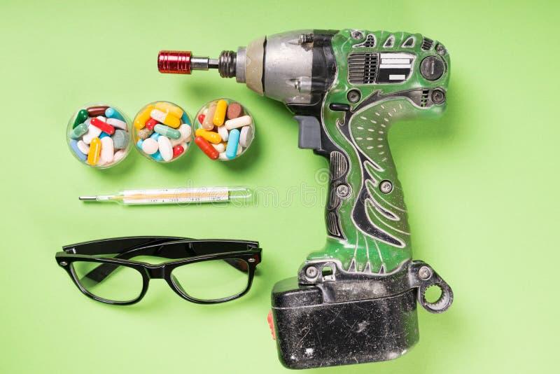 Três copos de comprimidos coloridos furam vidros e termômetro imagens de stock