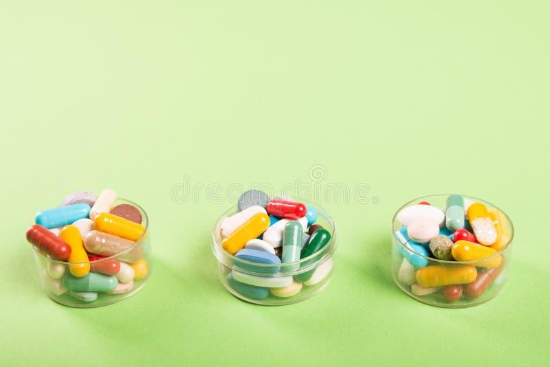 Três copos de comprimidos e de tabuletas coloridos fotos de stock royalty free