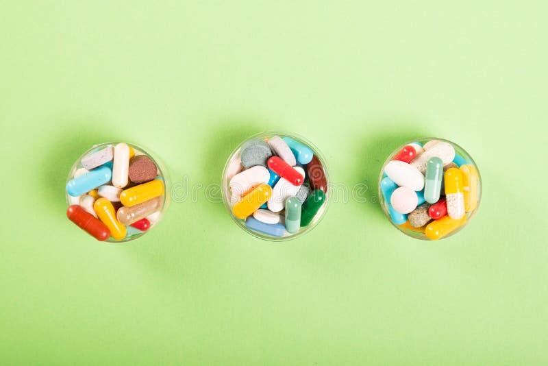 Três copos de comprimidos e de tabuletas coloridos imagens de stock royalty free