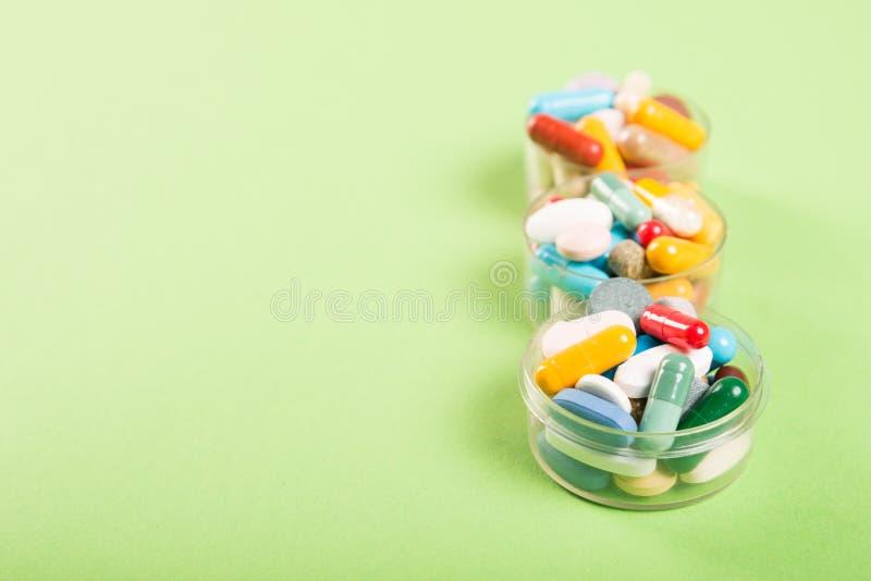 Três copos de comprimidos e de tabuletas coloridos fotos de stock