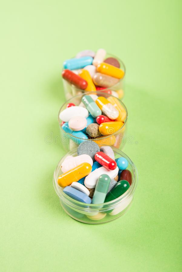 Três copos de comprimidos e de tabuletas coloridos foto de stock royalty free