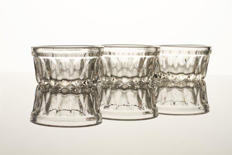Três copos de vidro na tabela reflexiva fotos de stock