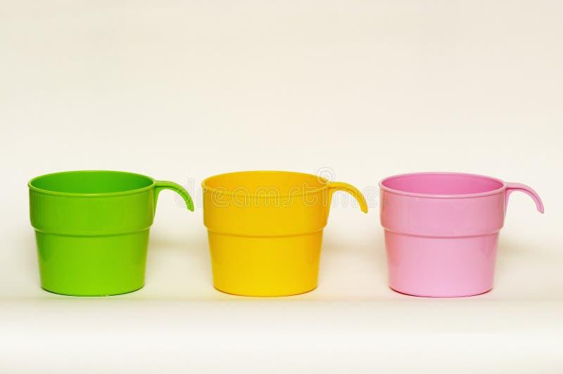 Três copos plásticos coloridos fotos de stock royalty free