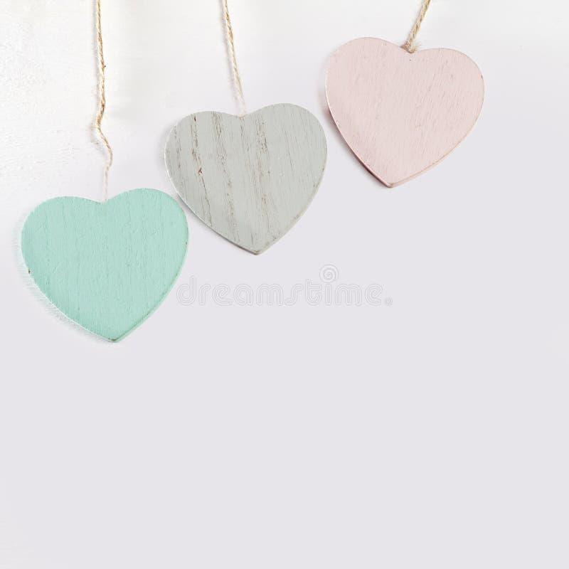 Três corações de madeira penduram em uma parede de madeira branca fotografia de stock