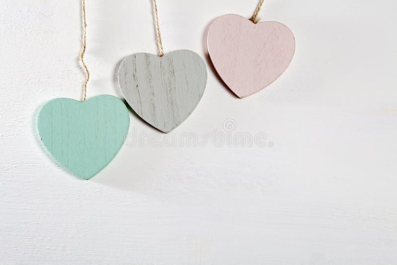 Três corações de madeira penduram em uma parede de madeira branca imagem de stock royalty free