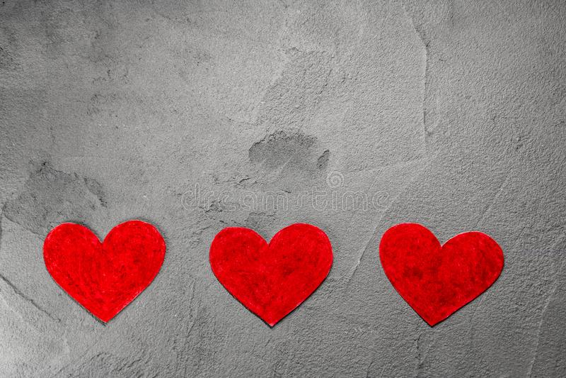 Três corações de papel vermelhos na parede cinzenta com espaço da cópia imagens de stock royalty free