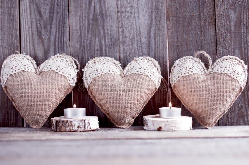 Três corações feitos a mão do pano de saco com laço imagens de stock royalty free