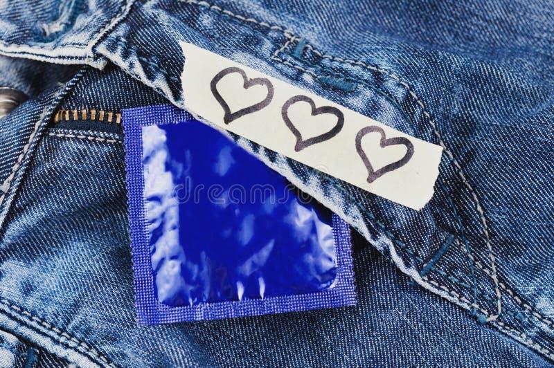 Três corações representados no papel e no preservativo rasgados no pacote azul da folha em calças de brim imagens de stock royalty free