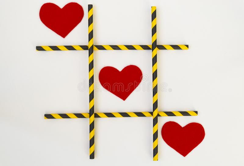 Três corações sentidos vermelhos são alinhados em um jogo do tique-TAC-dedo do pé, em uma grade em um fundo branco A grade consis fotos de stock royalty free