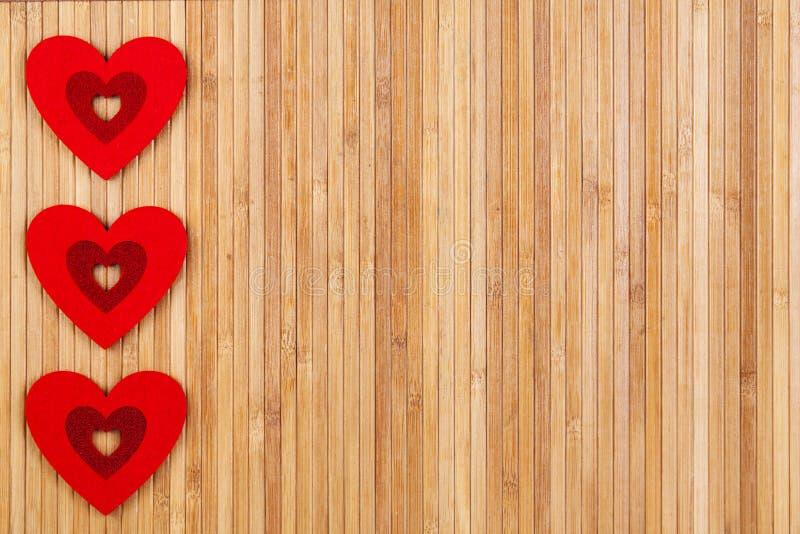 Três corações vermelhos em um fundo de madeira, um dia do ` s do Valentim do forte do cartão fotografia de stock