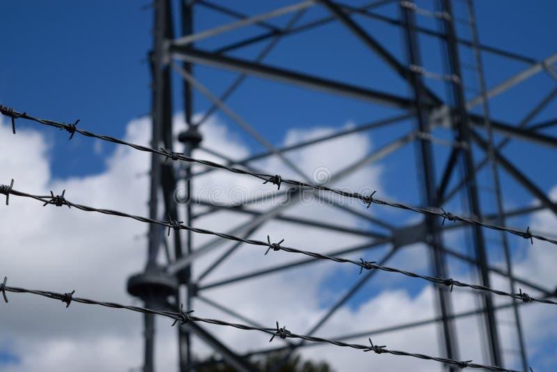 Três costas do arame farpado com a torre de comunicações no fundo foto de stock