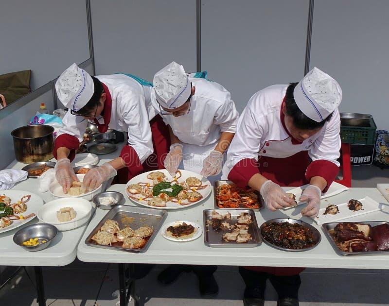Três cozinheiros chefe em uma competição de cozimento fotos de stock royalty free