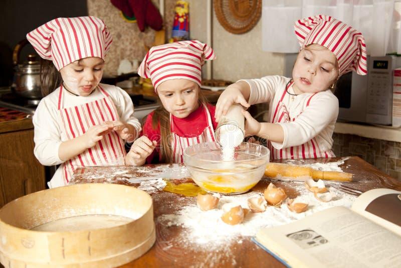 Três cozinheiros chefe pequenos na cozinha foto de stock