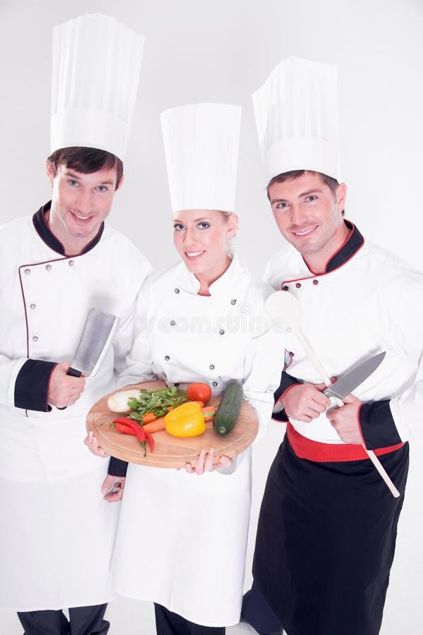Três cozinheiros chefe que levantam com placa vegetal foto de stock royalty free