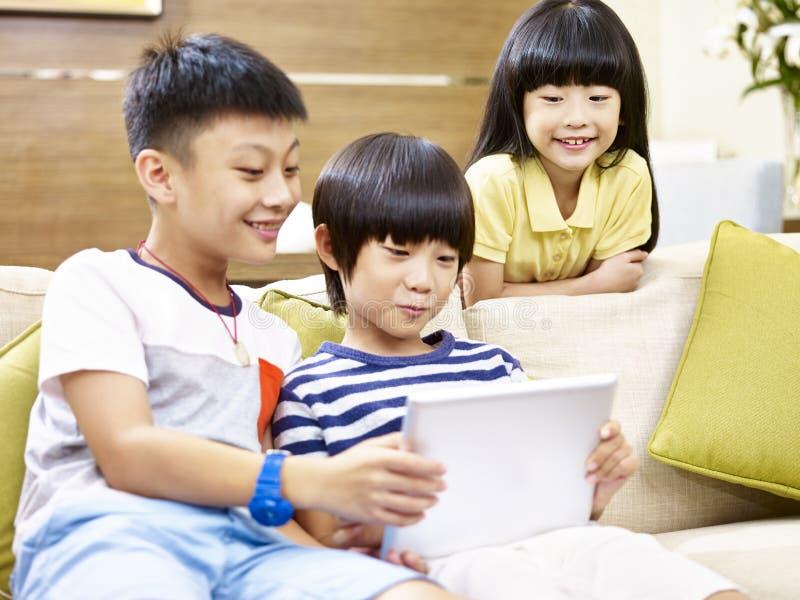 Três crianças asiáticas que jogam com tabuleta digital fotografia de stock